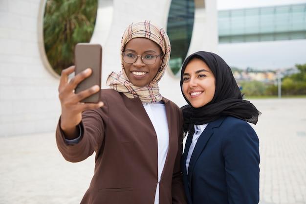Glückliche weibliche bürofreunde, die draußen selfie nehmen