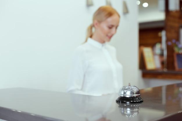 Glückliche weibliche empfangsdame, die am hotelzähler steht
