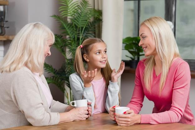 Glückliche weibliche generation sprechen miteinander in der küche