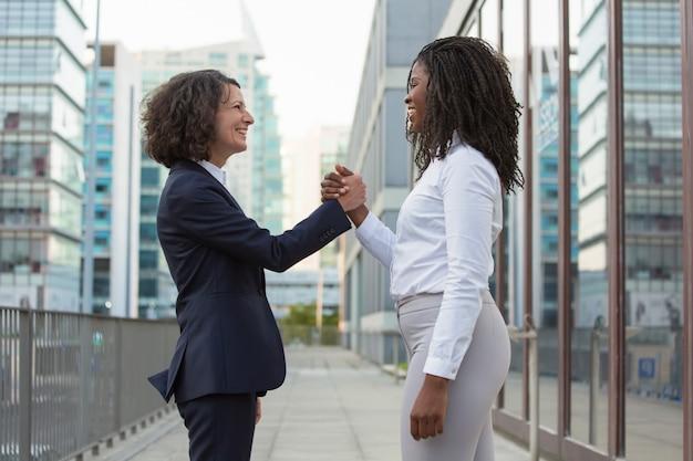 Glückliche weibliche geschäftskollegen, die teamerfolg feiern