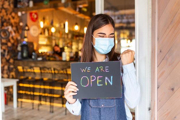 Glückliche weibliche kellnerin mit schützender gesichtsmaske, die offenes schild hält, während sie an der tür des cafés oder des restaurants steht, offen nach dem sperren wegen des ausbruchs des coronavirus covid-19 wieder