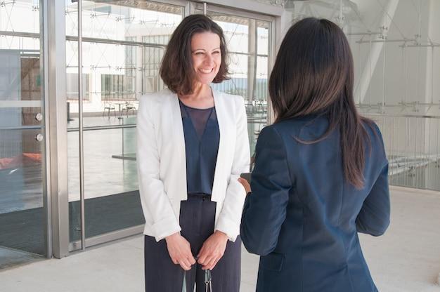 Glückliche weibliche kollegen, die in der bürohalle sprechen