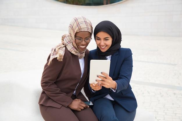 Glückliche weibliche mitarbeiter, die inhalt auf tablette aufpassen
