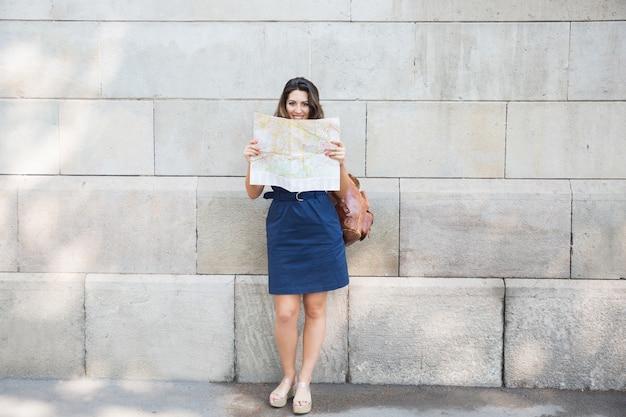 Glückliche weibliche reiseberaterkarte in der straße