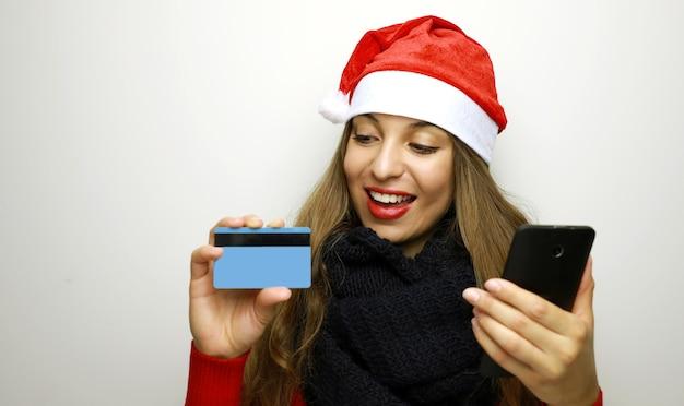 Glückliche weihnachtsfrau beim einkaufen mit kreditkarte und handy