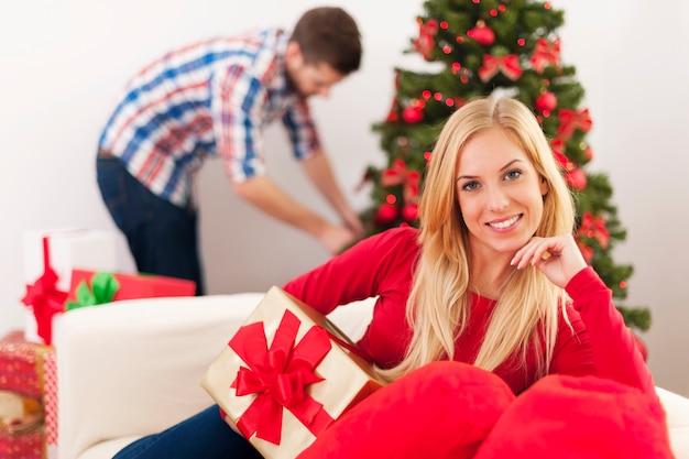 Glückliche weihnachtsfrau, die auf sofa im wohnzimmer sitzt