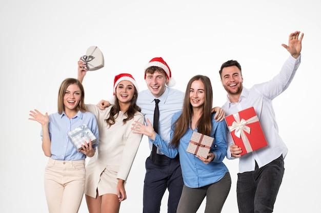 Glückliche weihnachtsfreunde, die weihnachtsmützen mit geschenken in den händen auf einem weißen hintergrund tragen. neujahr, weihnachten, feiertag.