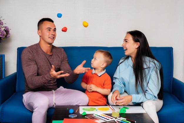 Glückliche weiße familie genießen und spielen zu hause. mama, papa und sohn lachen, malen und formen mit plastilin