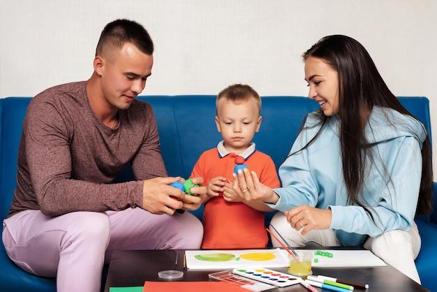 Glückliche weiße familie sind mit kreativer arbeit beschäftigt und haben spaß zu hause. mama, papa und kleiner sohn malen und formen mit plastilin