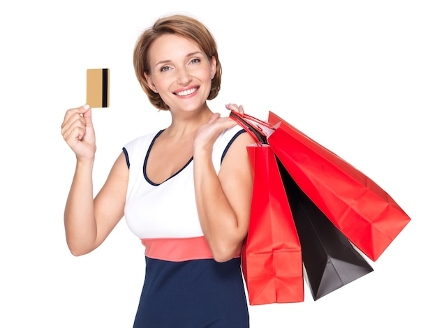 Glückliche weiße frau mit einkaufstüten und kreditkarte über leerraum
