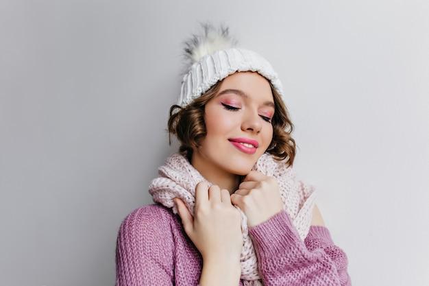 Glückliche weiße lockige frau im wollpullover. innenporträt des schönen mädchens mit rosa make-up, das im hut und im schal am kalten tag aufwirft.
