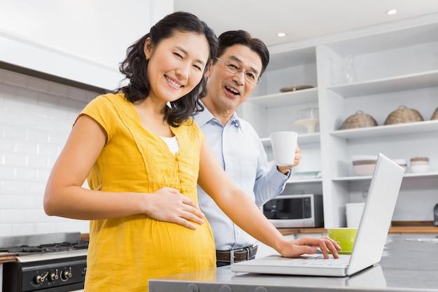 Glückliche werdende paare unter verwendung des laptops in der küche