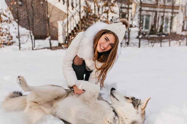 Glückliche winterzeit der erstaunlichen lächelnden frau, die mit dem heiseren hund im schnee spielt. charmante junge frau mit langen brünetten haaren, die spaß mit haustier auf straße voller schnee haben. helle wahre emotionen.
