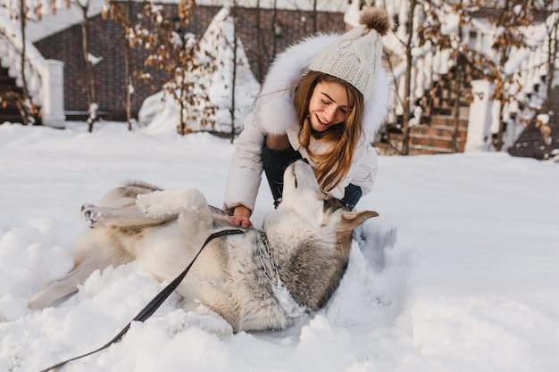 Glückliche winterzeit der freudigen jungen frau, die mit niedlichem husky hund im schnee auf straße spielt. fröhliche stimmung, positive emotionen, echte freundschaft mit haustieren, liebestiere