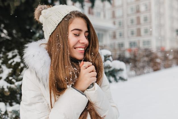 Glückliche winterzeit der jungen freudigen frau, die schnee in der stadt genießt. attraktive frau, langes brünettes haar, lächelnd mit geschlossenen augen.