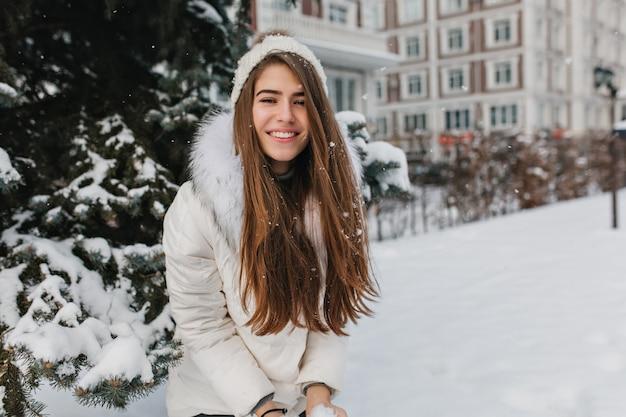 Glückliche winterzeit der positiven hübschen frau, die mit schnee spielt. lächelnde junge frau mit langen brünetten haaren, die wochenende während des spaziergangs die straße hinunter in frostigem tag genießen ..