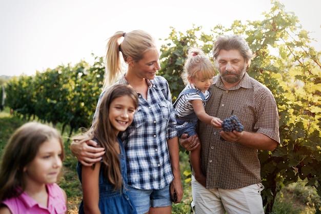 Glückliche winzerfamilie im weinberg vor der ernte