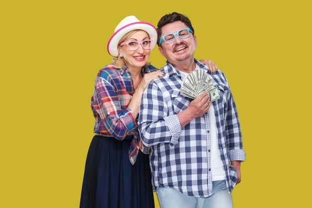 Glückliche wohlhabende familie, erwachsener mann und frau in lässig kariertem hemd stehen pickaback zusammen, halten dollar-fan, zahniges lächeln, blick in die kamera. innen, isoliert, studioaufnahme, gelber hintergrund