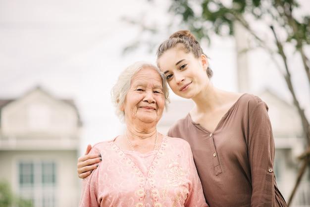 Glückliche youg frau, die ältere frau umarmt