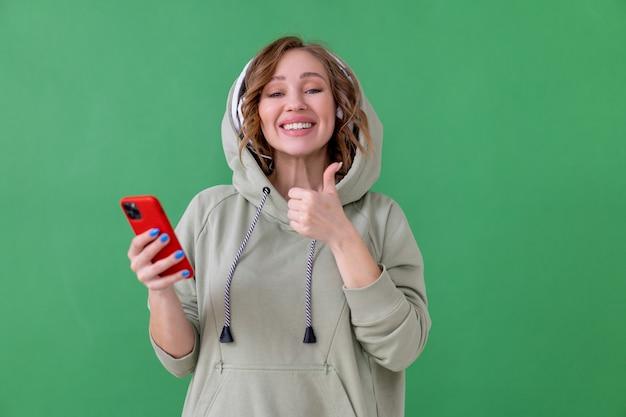 Glückliche zähne lächeln frau hören musikkopfhörer, die smartphone in der hand halten, zeigen daumen hoch geste