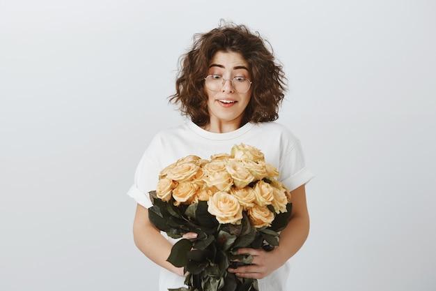Glückliche zarte freundin erhalten blumenstrauß von schönen blumen, hält rosen und seufzt überrascht