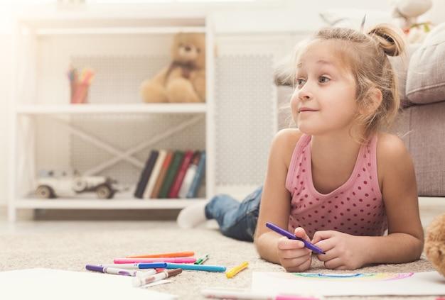 Glückliche zeichnung des kleinen mädchens. nettes kind, das zu hause auf dem boden zwischen farbigem papier und bleistiften liegt. diy, kreatives kunsthobby, frühes entwicklungs- und inspirationskonzept