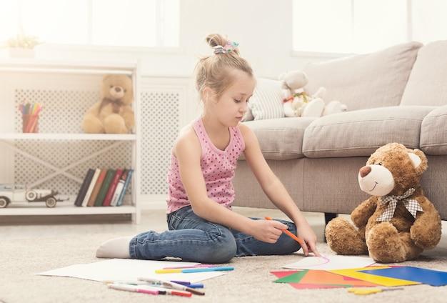 Glückliche zeichnung des kleinen mädchens. nettes kind, das zu hause auf dem boden zwischen farbigem papier und bleistiften sitzt. diy, kreatives kunsthobby, frühes entwicklungs- und inspirationskonzept
