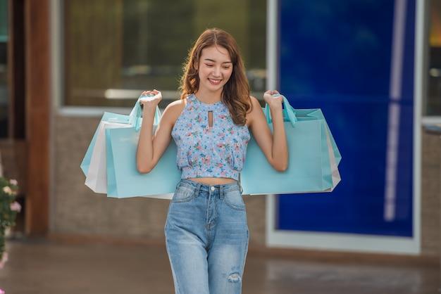 Glückliche zeit zum einkaufskonzept, asiatin, die einkaufstaschen in der mallmitte hält.