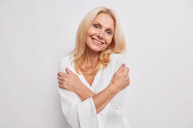 Glückliche zufriedene frau mittleren alters umarmt sich selbst lächelt sanft zeigt weiße zähne kippt den kopf in seidenbluse gekleidet isoliert über weißer wand hat einen romantischen, zarten ausdruck, der liebe braucht