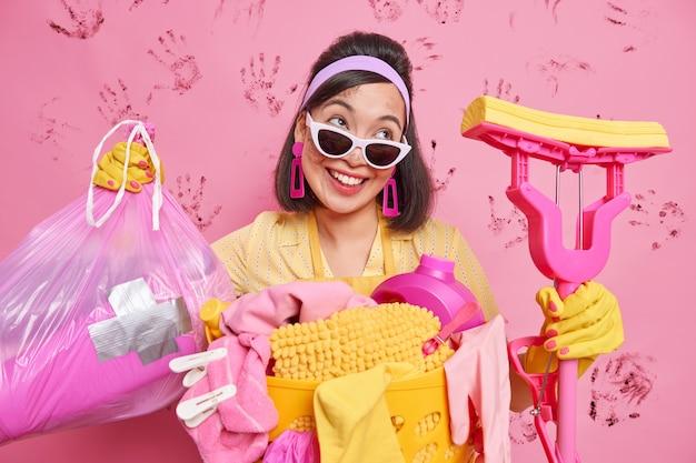 Glückliche zufriedene hausfrau putzt haus trägt mopp und müllsack gibt professionellen reinigungsservice sieht gerne weg trägt sonnenbrille gummischutzhandschuhe isoliert über rosa wand