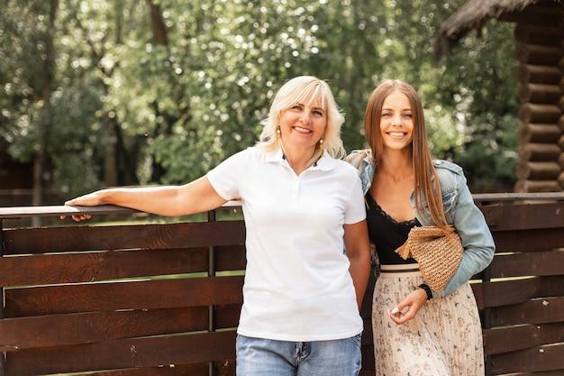 Glückliche zwei ältere mutter und schöne tochter mit einem lächeln in einer modischen jeansjacke mit einem weißen poloshirt in blue jeans mit einer gewebten handtasche in der nähe eines holzzauns im dorf