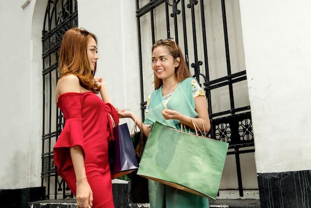 Glückliche zwei asiaten mit der einkaufstascheunterhaltung