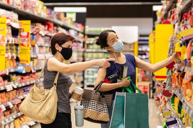 Glückliche zwei asiatische freundinnen, die ermäßigte produkte im supermarkt kaufen?