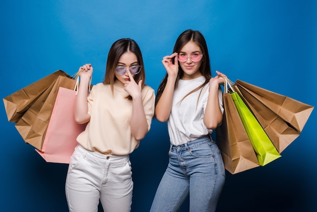 Glückliche zwei frauen mit bunten einkaufstaschen auf blauer wand