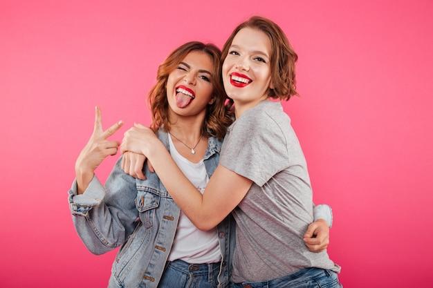 Glückliche zwei freundinnen, die friedensgeste zeigend umarmen