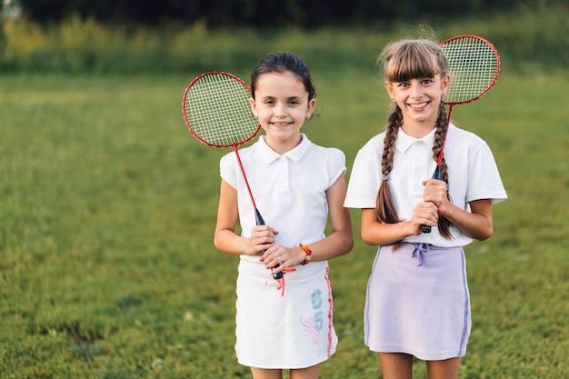 Glückliche zwei freundinnen, die in der hand badminton halten