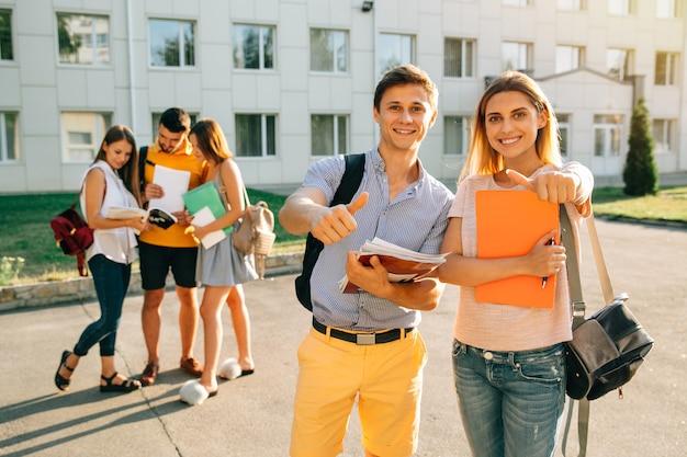 Glückliche zwei junge studenten mit den notizbüchern und rucksäcken, die daumen lächeln und sich zeigen