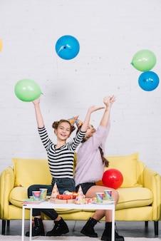 Glückliche zwei mädchen, die das werfen von ballonen in der luft auf partei genießen