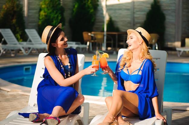 Glückliche zwei mädchen, die in der nähe des pools auf liegestühlen sonnenbaden