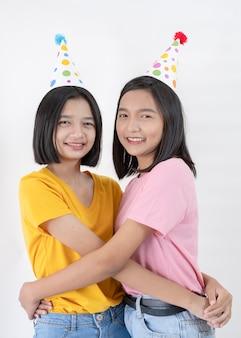 Glückliche zwei mädchen tragen partyhut auf weißem hintergrund