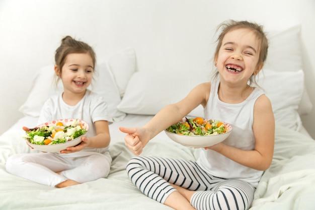 Glückliche zwei niedliche kinder, die gemüsesalat im schlafzimmer auf dem bett essen. gesundes essen für kinder und jugendliche.