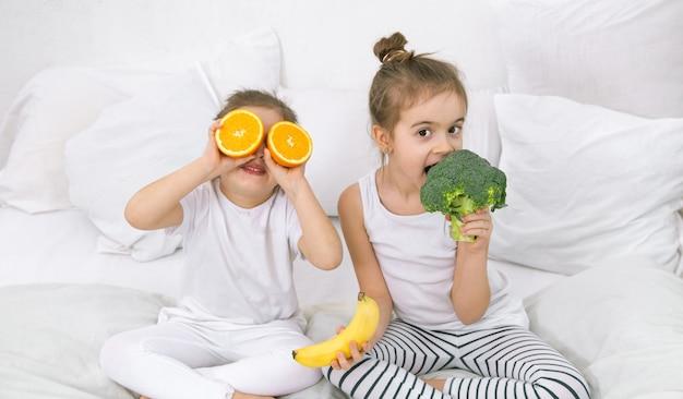 Glückliche zwei niedliche kinder, die mit obst und gemüse spielen.