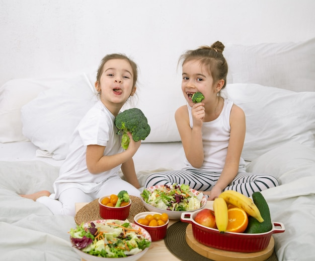 Glückliche zwei niedliche mädchen, die obst und gemüse im schlafzimmer auf dem bett essen. gesundes essen für kinder und jugendliche.