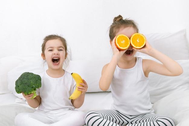 Glückliche zwei süße kinder spielen mit obst und gemüse auf dem bett. gesundes essen für kinder.