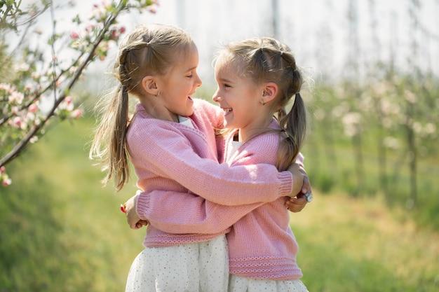 Glückliche zwillingsschwestern umarmen vor dem hintergrund eines grün blühenden apfelgartens. die schwestern sehen sich an und lachen.