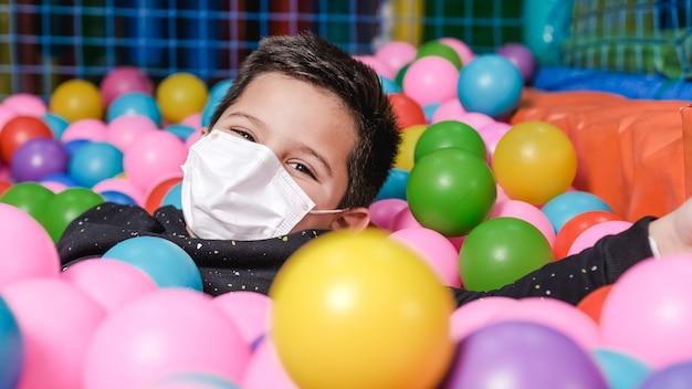 Glücklicher 5-jähriger junge mit maske in einem ballpool, der bälle zur kamera wirft