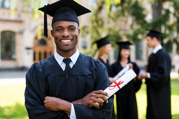 Glücklicher absolvent. glücklicher afrikanischer mann in abschlusskleidern, der diplom hält und lächelt, während seine freunde im hintergrund stehen