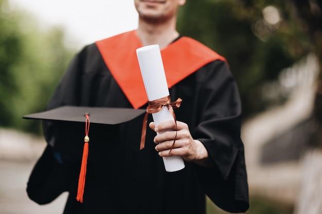 Glücklicher absolvent im kleid hält ein diplom des abschlusses