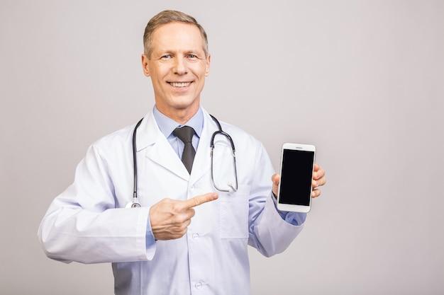 Glücklicher älterer arztmann, der einen leeren smartphonebildschirm lokalisiert auf einem grauen hintergrund zeigt.