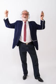 Glücklicher älterer bärtiger geschäftsmann, der lächelt, während er musik hört und handy mit geschlossenen augen auf weiß hält